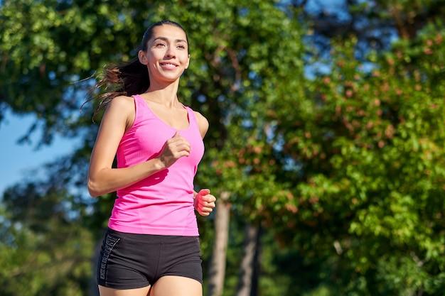 Mujer corriendo corredor femenino trotar durante el ejercicio al aire libre en un parque. hermosa mujer en forma. modelo de fitness al aire libre. pérdida de peso