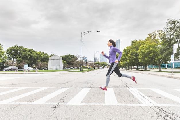 Mujer corriendo y cruzando la carretera en cebra en chicago