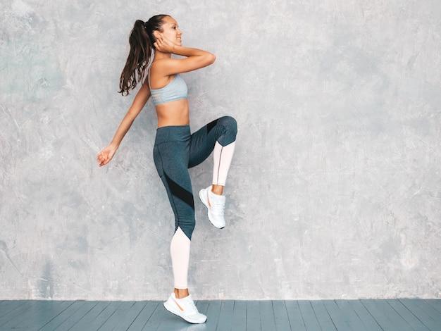 Mujer corriendo en estudio cerca de la pared gris