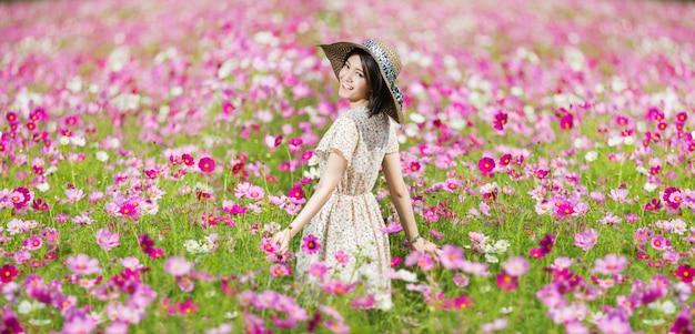 Mujer corriendo en el jardín florece flores de cosmos para tocarla.