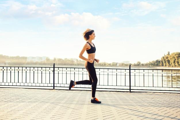 Mujer corriendo por el lago al atardecer