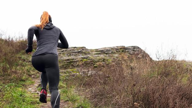 Mujer corriendo en la naturaleza desde atrás shot