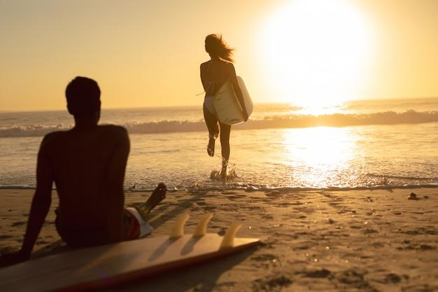 Mujer corriendo con tabla de surf mientras el hombre se relaja en la playa durante el atardecer