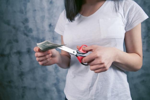 Mujer corta billete de un dólar con tijeras en gris