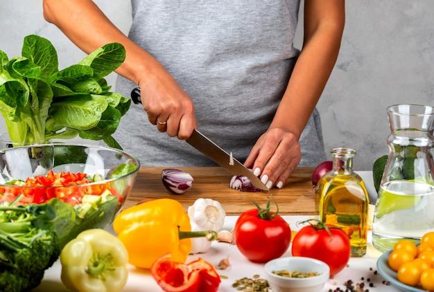 Mujer corta cebollas y hace ensalada en la cocina