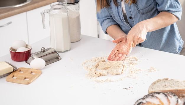 Mujer corta un cortador de galletas de masa sobre un fondo blanco de mesa de cocina.