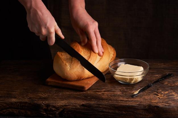 Mujer corta pan recién horneado en mesa de madera cerca del tazón con mantequilla en negro