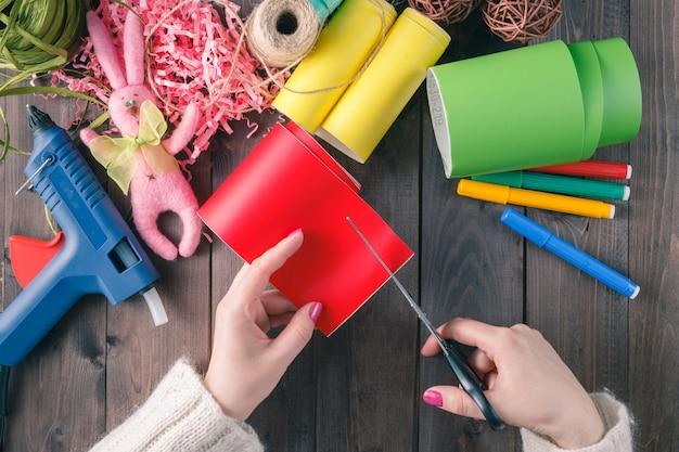 Mujer corta papel de color rojo
