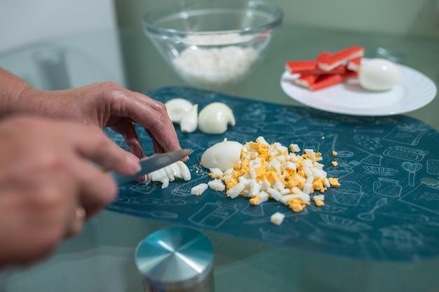 Una mujer corta un primer plano de huevo de gallina