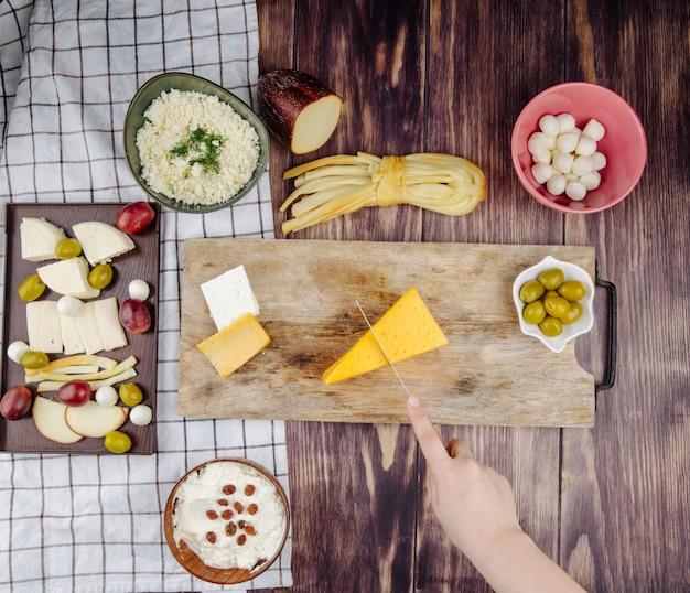 Una mujer corta queso holandés en una tabla para cortar madera con aceitunas en vinagre y varios tipos de queso en la vista superior rústica