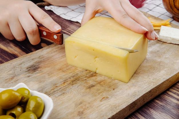 Una mujer corta queso holandés en una vista lateral del tablero de madera