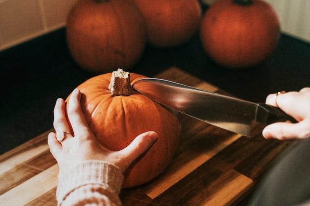 Mujer cortando calabaza para la fotografía de comida de la cena de acción de gracias