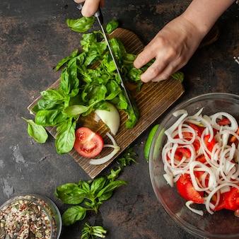 Mujer cortando espinacas para vista superior de ensalada de temporada