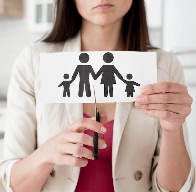 Mujer cortando papel familia con tijeras