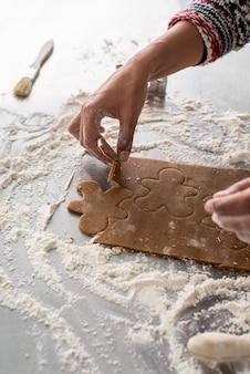 Mujer cortando un poco de masa de pan de jengibre con hombre cortador de galletas de metal