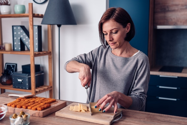 Mujer cortando queso gouda sobre tabla para cortar madera