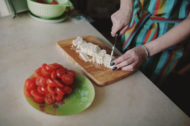 Mujer cortando queso