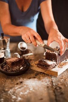 Una mujer cortando rebanada de pastel con un cuchillo en la tabla de cortar