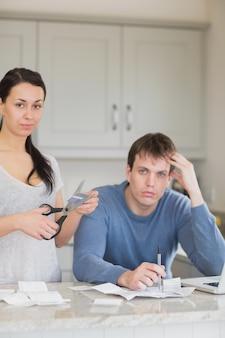 Mujer cortando la tarjeta de crédito con el hombre calculando las finanzas