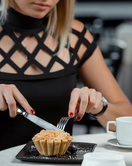 Mujer cortando una tarta de manzana en el restaurante