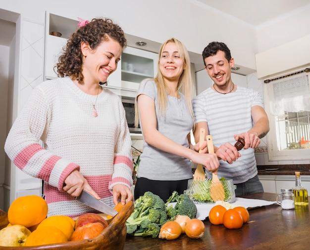 Mujer cortando verduras y joven pareja preparando ensalada en la cocina