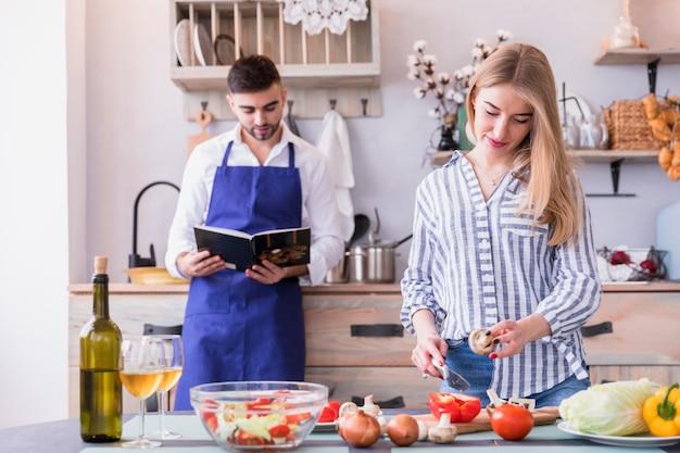 Mujer cortando verduras mientras que hombre leyendo libro de recetas