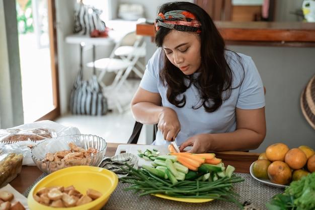 Mujer cortando zanahorias para la cena