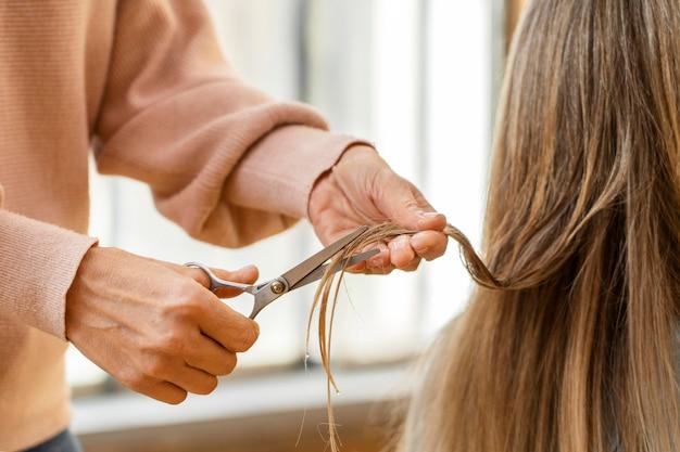 Mujer cortándose el pelo en casa por peluquero
