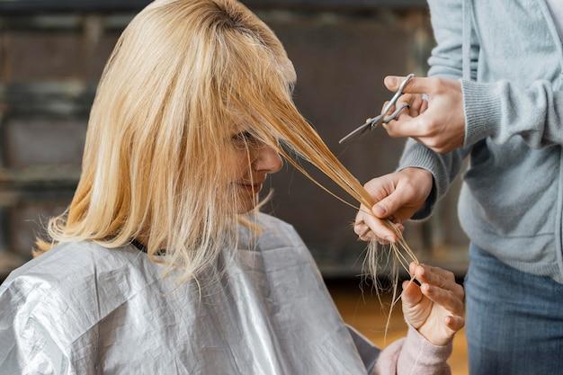 Mujer cortándose el pelo por peluquero en casa