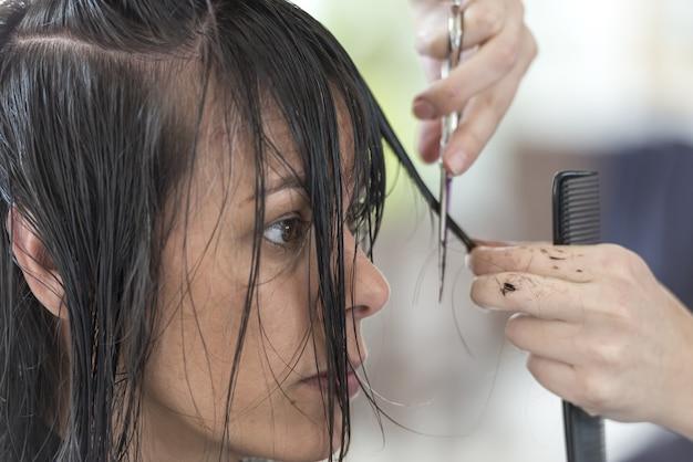 Mujer cortándose el pelo en un salón de belleza