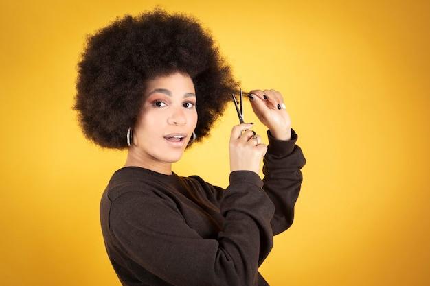 Mujer cortándose el pelo con unas tijeras
