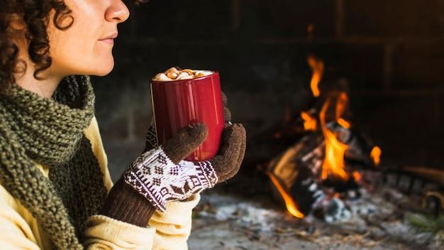Mujer de la cosecha con la bebida caliente cerca de la chimenea