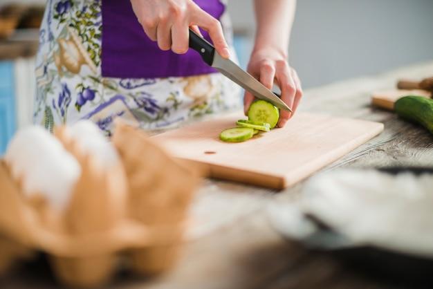 Mujer de la cosecha cortando pepino