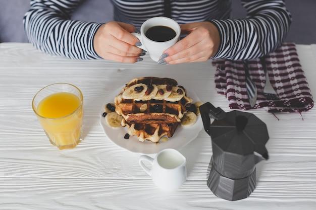 Mujer de la cosecha desayunando con gofres y café