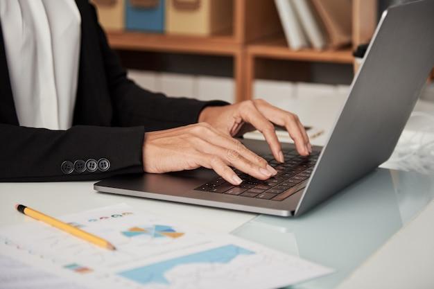 Mujer de cosecha escribiendo en la computadora portátil