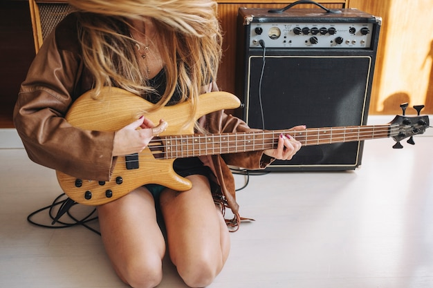 Mujer de la cosecha con la guitarra cerca del amplificador