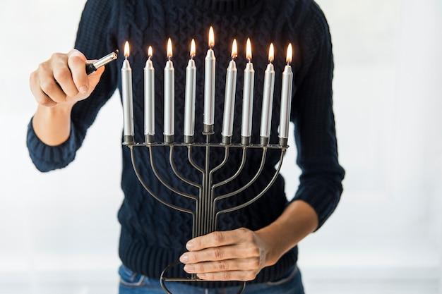 Mujer de la cosecha que enciende velas en menorah del metal