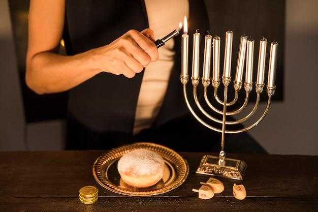 Mujer de la cosecha que enciende velas en menorah