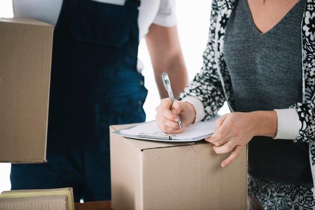 Mujer de la cosecha que firma en la caja del cartón