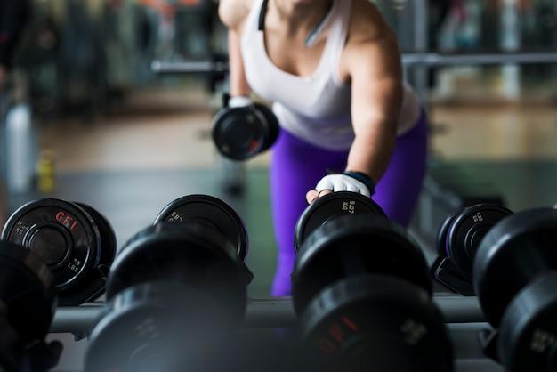 Mujer de la cosecha que levanta pesa de gimnasia en gimnasio