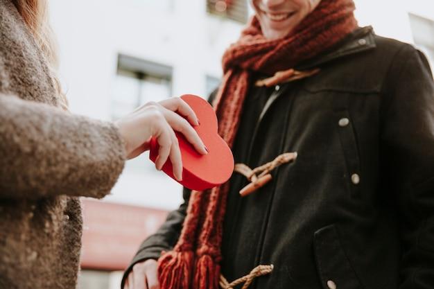 Mujer de la cosecha que regala la caja presente del corazón al novio