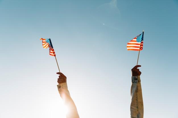 Mujer de la cosecha que sostiene banderas americanas contra el cielo azul