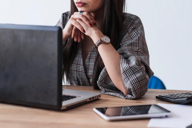Mujer de la cosecha que usa la computadora portátil y el pensamiento