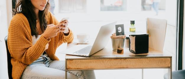 Mujer de la cosecha que usa smartphone en café