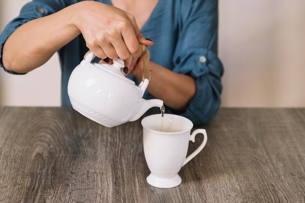 Mujer de cosecha vertiendo té