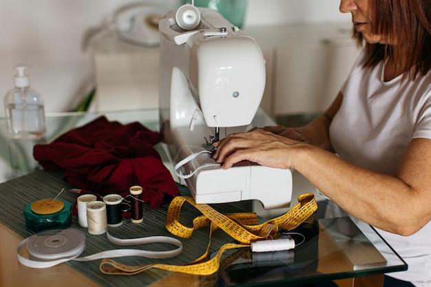 Mujer cosiendo mascarilla de tela para la familia