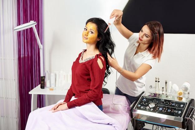 Mujer cosmetóloga está dando tratamiento capilar a una cliente morena con una máscara de oro en la cara en un moderno salón de belleza.
