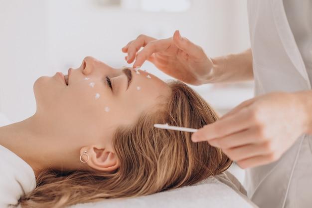 Mujer en cosmetóloga con tratamiento de belleza