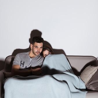 Mujer en coverlet y hombre guapo viendo la televisión en el sofá en una habitación oscura
