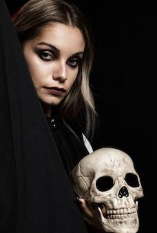 Mujer con cráneo y fondo negro
